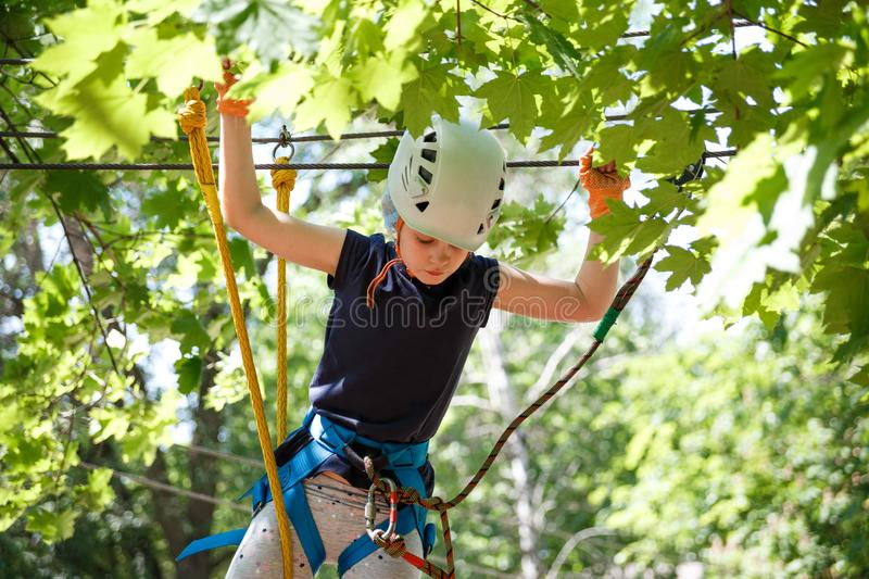 8 years old girl in forest adventure park. Child climb on high rope trail. Outdoor playground with rope way stock photography