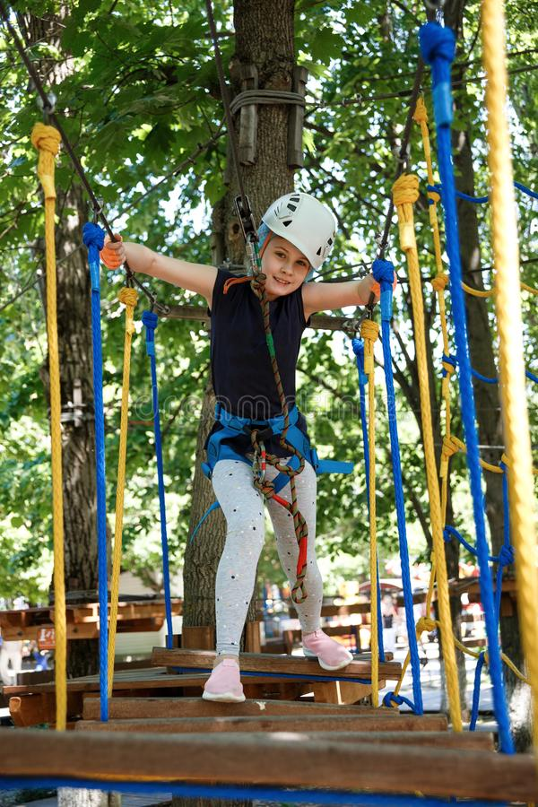 8 years old girl in forest adventure park. Child climb on high rope trail. Outdoor playground with rope way stock images
