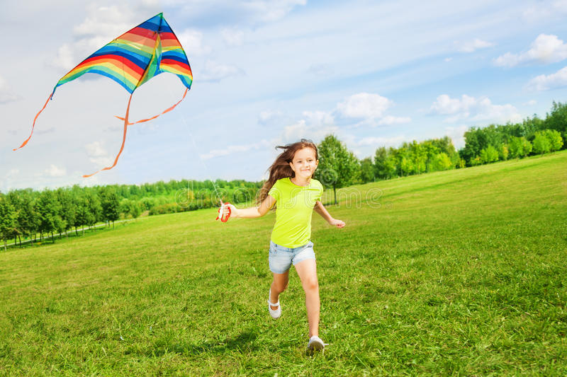 6 years old girl running with kite. Little cute 7 years old girl running in the field with kite on summer day stock photos