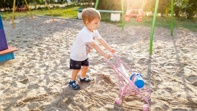 3 years old little boy with toy pram for dolls playing on the playground at park royalty free stock images