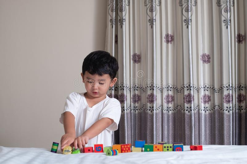 3 years old little cute Asian boy play toy or square block puzzle at home on the bed, kid lying learn by playing block shape or p stock photo