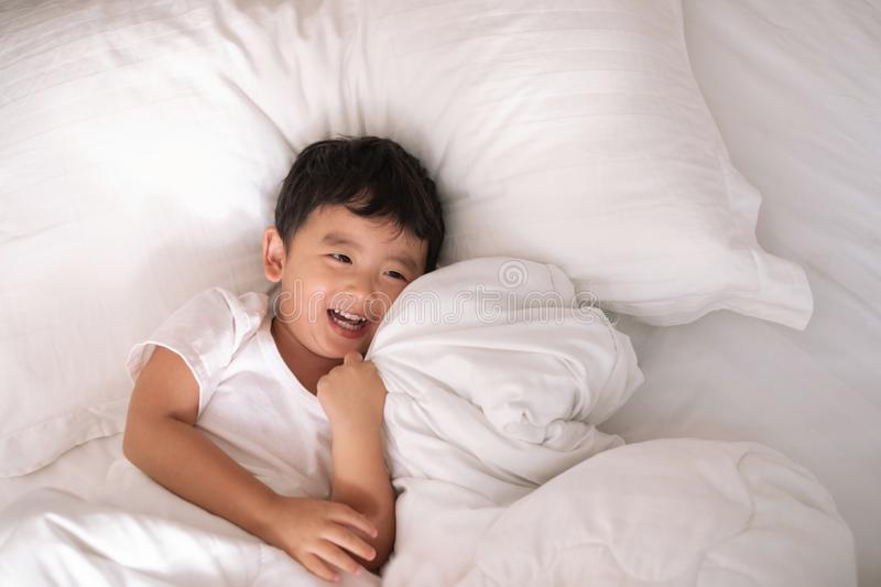 3 years old little cute Asian boy at home on the bed, kid lying. 3 years old little cute Asian boy in white shirt at home on the bed, kid lying playing and royalty free stock photo