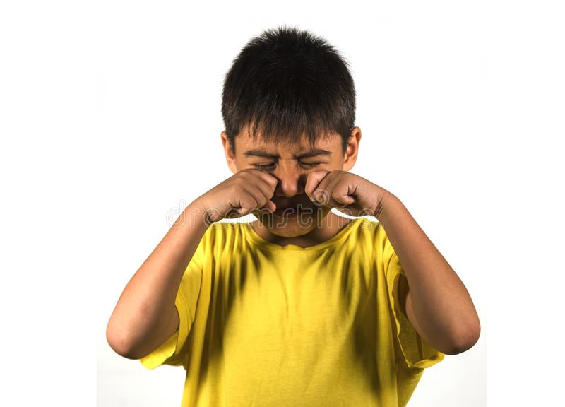7 or 8 years old male child crying helpless and sad isolated on white background wearing yellow t-shirt in kid scolded and nagged royalty free stock photo