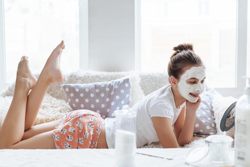 Girl making clay facial mask. 12 years old preteen relaxing on the sofa and making clay facial mask. Teenage girl doing anti blemish skin treatment. Morning skin stock images