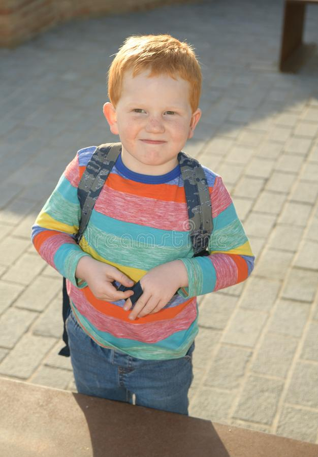 5 years old redheaded happy boy portrait. Looking at camera stock photo