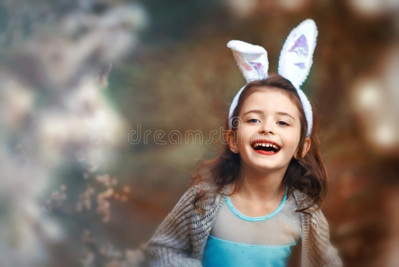 6 years old smiling girl with rabbit ears on head in blooming trees in spring. Child pretends to be easter bunny. Happy Easter royalty free stock photo