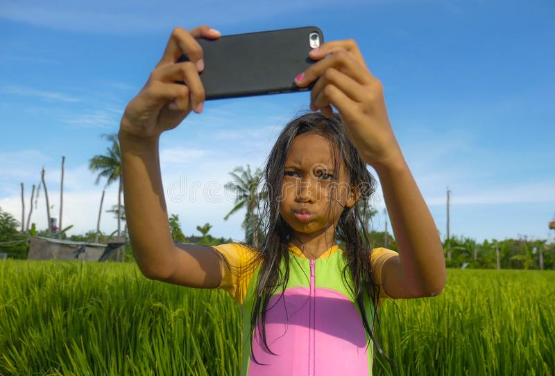 7 or 8 years old sweet and pretty female child outdoors at rice field landscape taking selfie portrait photo with mobile phone. Camera enjoying holidays in royalty free stock images