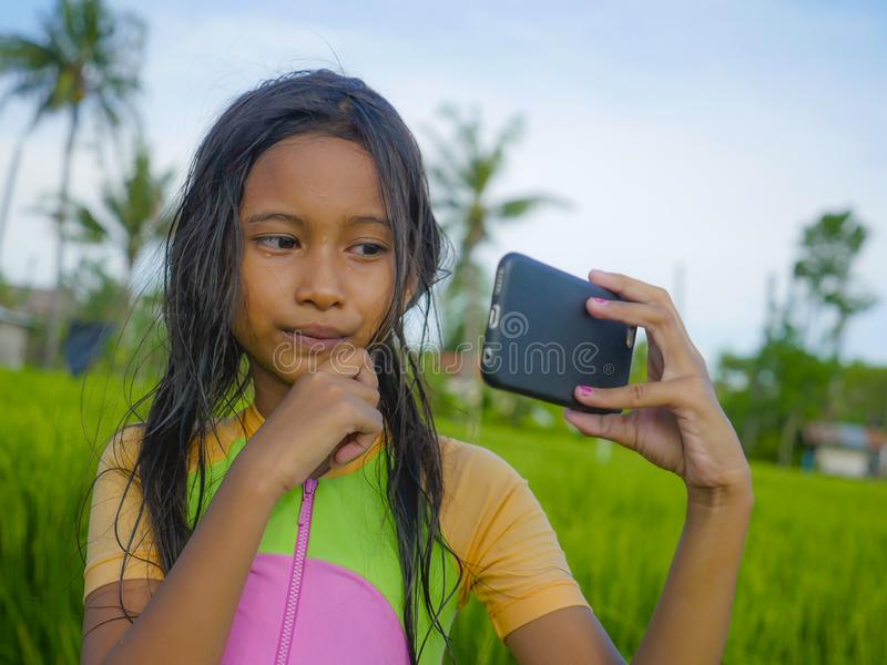 7 or 8 years old sweet and pretty female child outdoors at rice field landscape taking selfie portrait photo with mobile phone. Camera enjoying holidays in royalty free stock photo