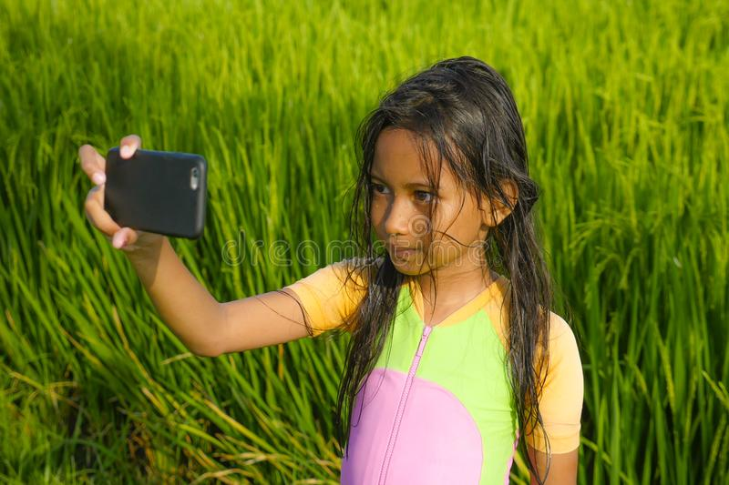 7 or 8 years old sweet and pretty female child outdoors at rice field landscape taking selfie portrait photo with mobile phone stock photography