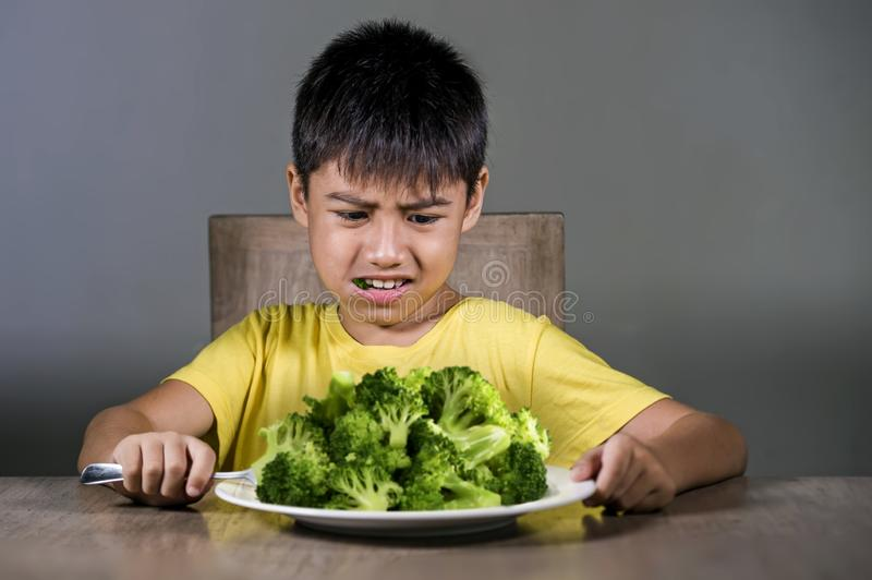7 or 8 years old upset and disgusted Asian kid sitting on table in front of broccoli plate looking unhappy rejecting the fresh. Food in child hate green stock photos