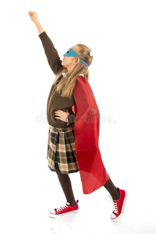 7 or 8 years old young female child in super hero costume over school uniform performing happy and excited isolated on white back. Ground in leadership success stock photography