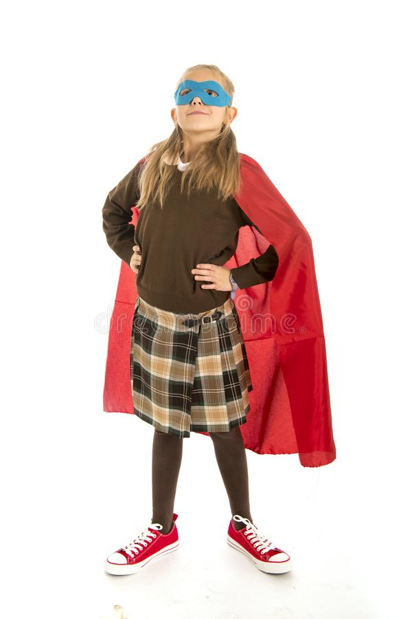 7 or 8 years old young female child in super hero costume over school uniform performing happy and excited isolated on white back. Ground in leadership success stock images