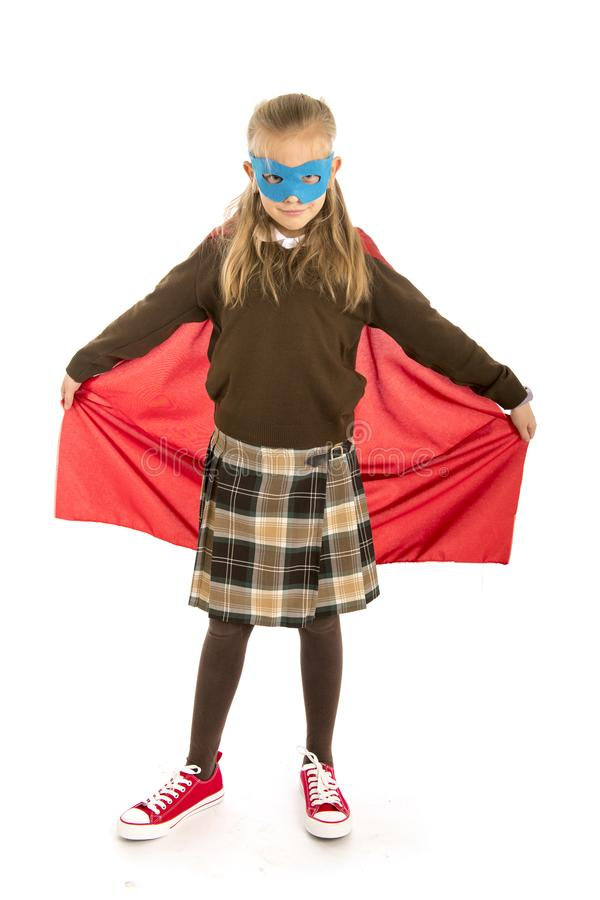 7 or 8 years old young female child in super hero costume over school uniform performing happy and excited isolated on white back. Ground in leadership success royalty free stock images