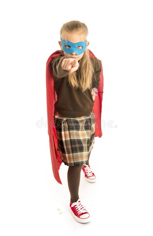7 or 8 years old young female child in super hero costume over school uniform performing happy and excited isolated on white back. Ground in leadership success royalty free stock photography