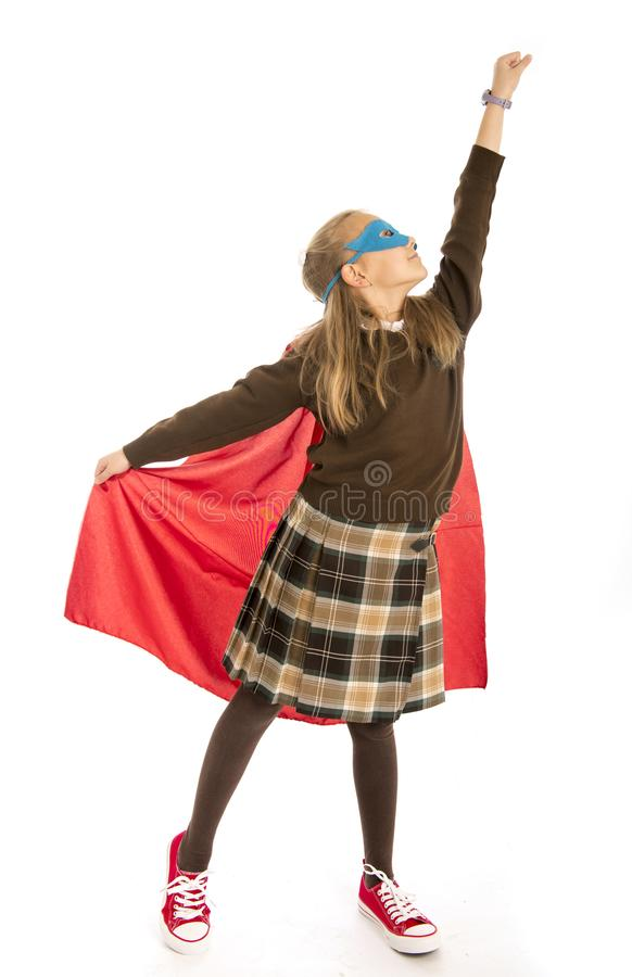 7 or 8 years old young female child in super hero costume over school uniform performing happy and excited isolated on white back. Ground in leadership success stock photo