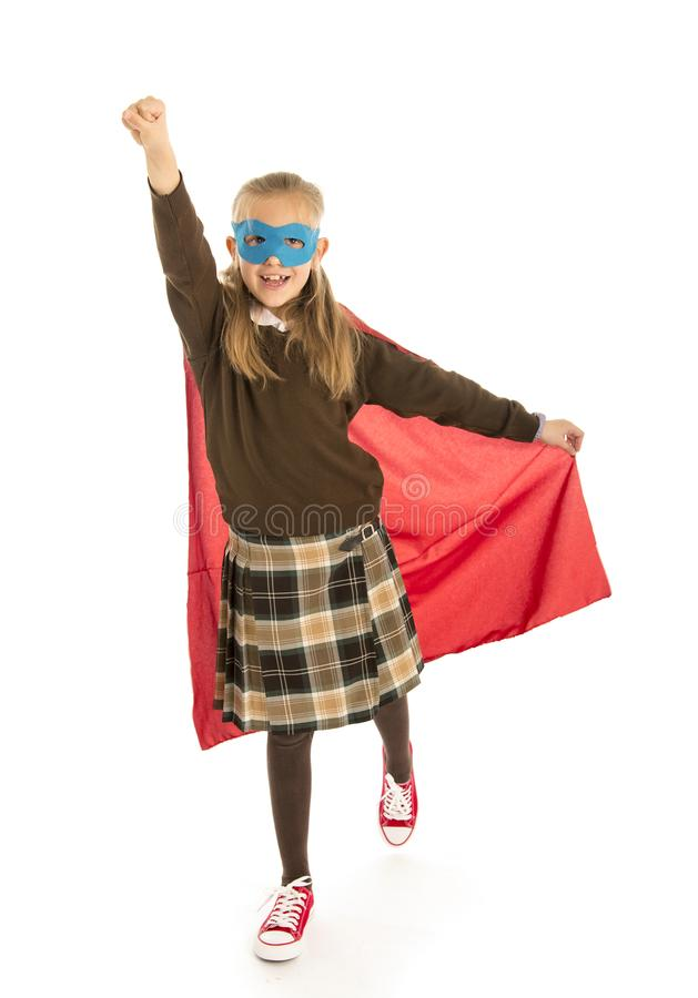 7 or 8 years old young female child in super hero costume over school uniform performing happy and excited isolated on white back. Ground in leadership success royalty free stock image