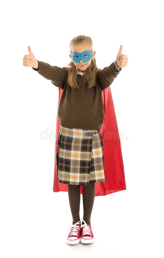 7 or 8 years old young female child in super hero costume over school uniform performing happy and excited isolated on white back. Ground in leadership success stock image