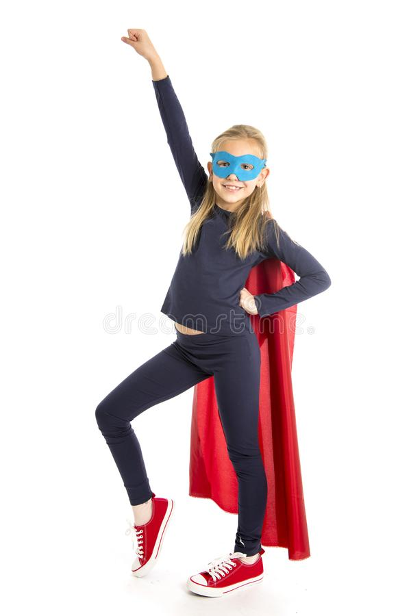 7 or 8 years old young female schoolgirl child in super hero costume performing happy and excited isolated on white background stock photo