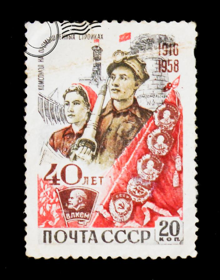 `40 years to Komsomol`, entitled `Komsomol at industrial constructions`. It shows young builders, circa 1958. MOSCOW, RUSSIA - JUNE 26, 2017: A stamp printed in royalty free stock image
