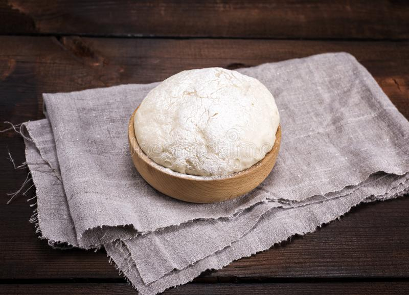 Yeast dough in a wooden bowl on a gray napkin stock photo
