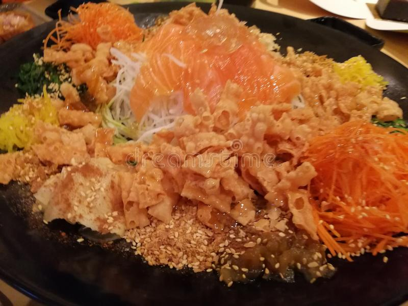 Yee Sang Prosperity Toss. Yusheng, yee sang or yuu sahng, or Prosperity Toss, also known as lo hei is a Teochew-style raw fish salad royalty free stock image