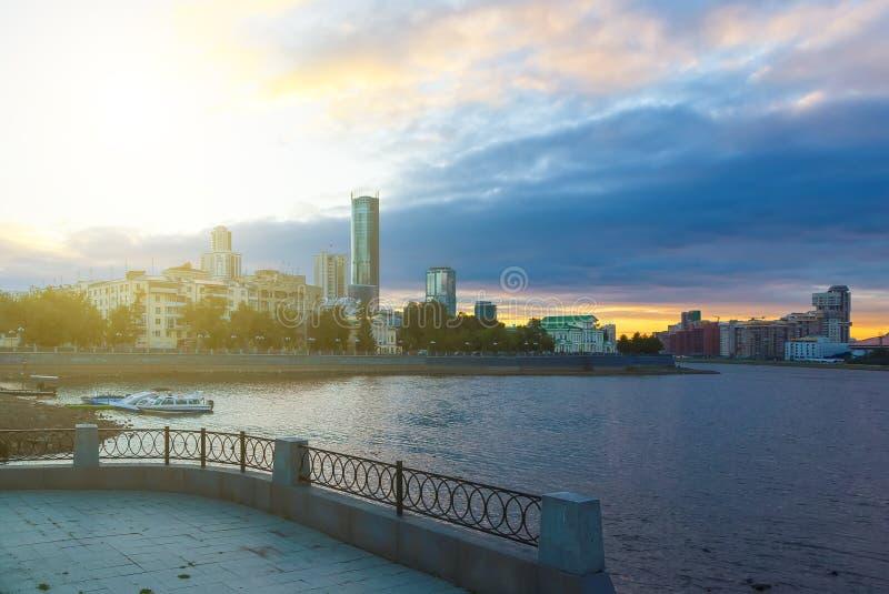 Yekaterinburg centrum på solnedgång Stadsdammsikt och att förbluffa moln och himmel Höga byggnader, skyskrapor på invallningen av fotografering för bildbyråer