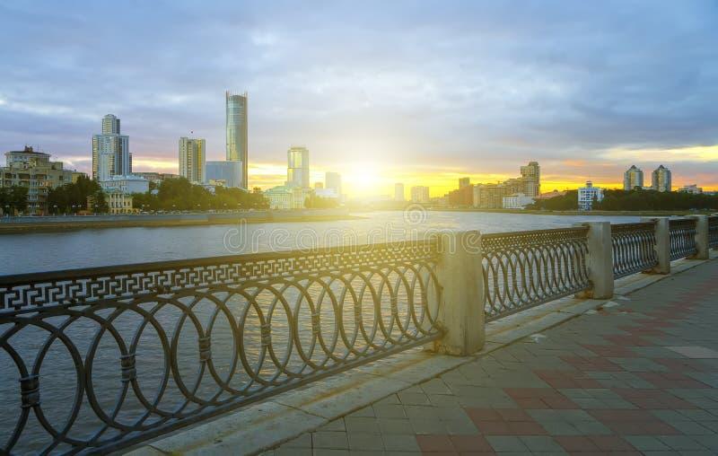 Yekaterinburg centrum på solnedgång Stadsdammsikt och att förbluffa moln och himmel Höga byggnader, skyskrapor på invallningen av arkivbilder