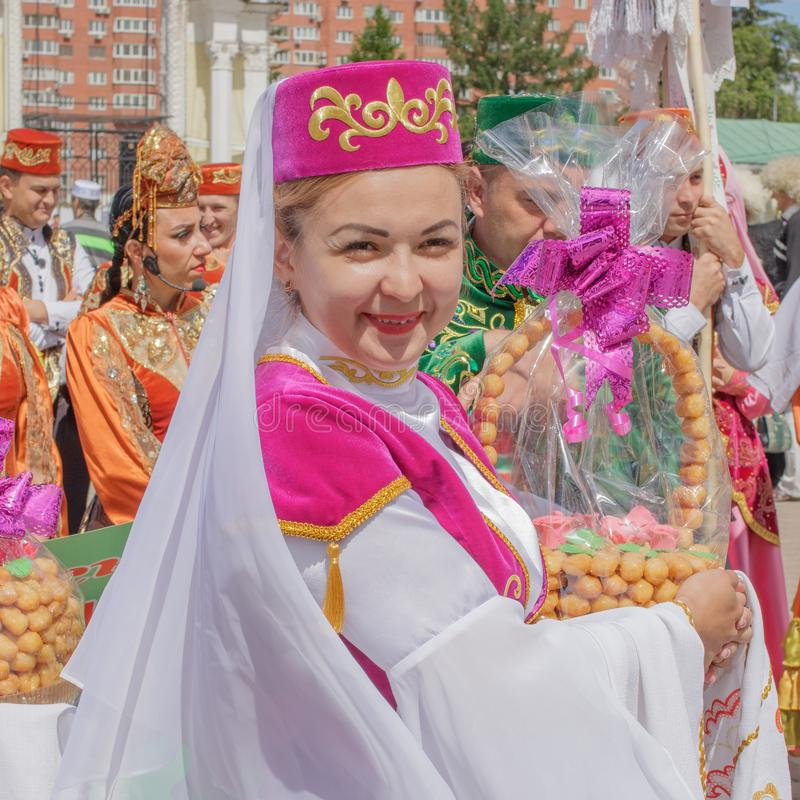 A woman in national clothes is holding a basket with the traditional Tatar cookies chak-chak and smiling stock photography