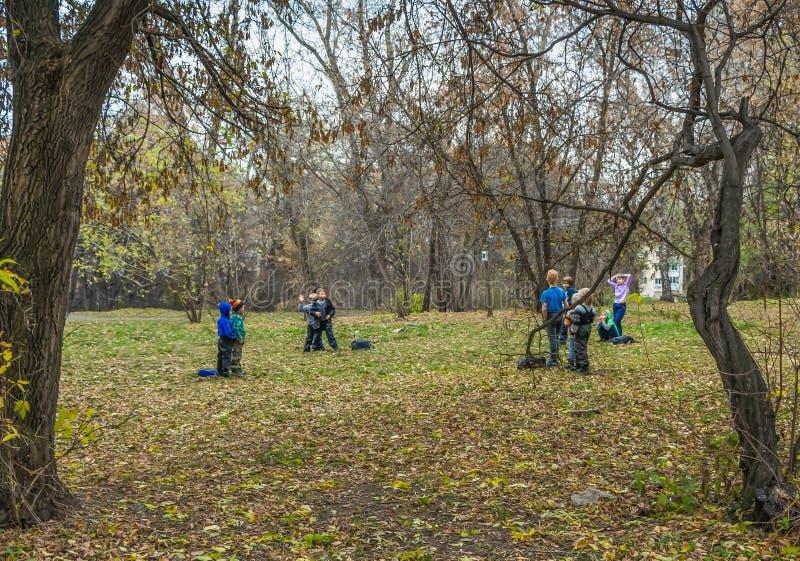 Yekaterinburg, Sverdlovsk Rusland - 10 19 2018: De jongere schoolkinderen spelen in een de herfstpark royalty-vrije stock foto