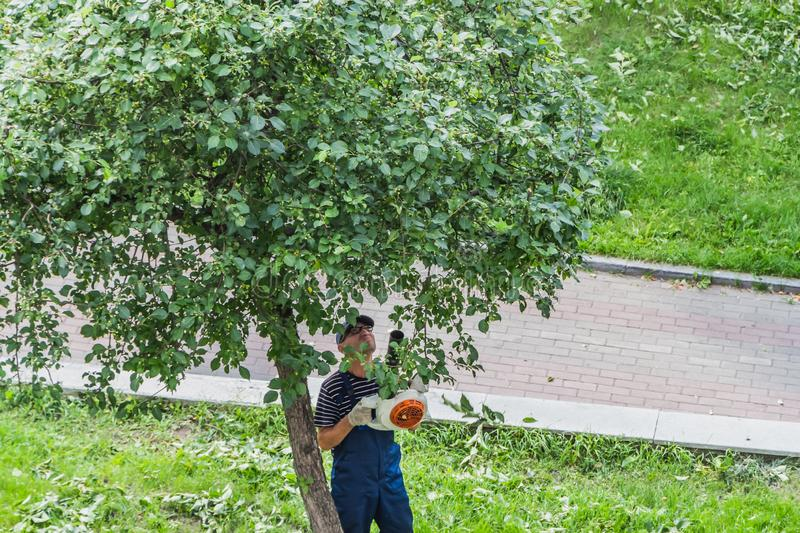 Yekaterinburg, Sverdlovsk Russia - 07 25 2018: A middle-aged man in a striped blue and white t-shirt and a blue work pants and stock photos
