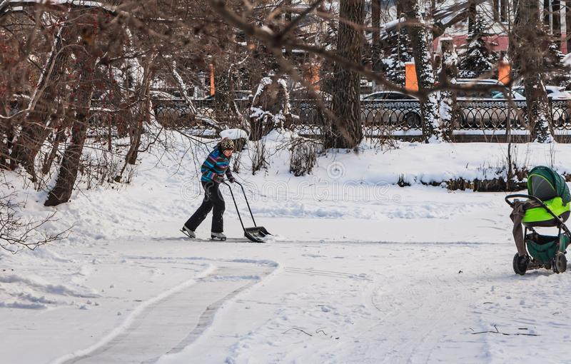Yekaterinburg, Sverdlovsk Russia - 11 27 2018: A young woman on white skates in a colorful jacket and black pants cleans an ice stock image