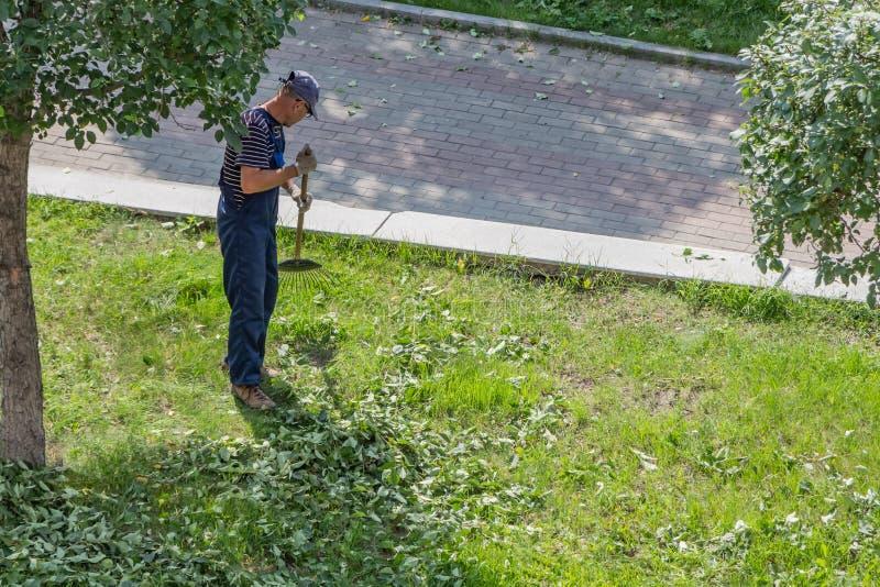 Yekaterinburg Sverdlovsk Ryssland - 07 25 2018: En medelålders man i randiga blå och vit t-skjorta och blåa för ett arbete flåsan arkivbild