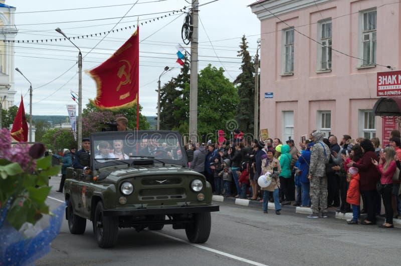 YELETS/LIPETSK, RUSIA - 9 DE MAYO DE 2017: los veteranos y los niños montan en un coche abierto debajo de la bandera roja fotos de archivo libres de regalías