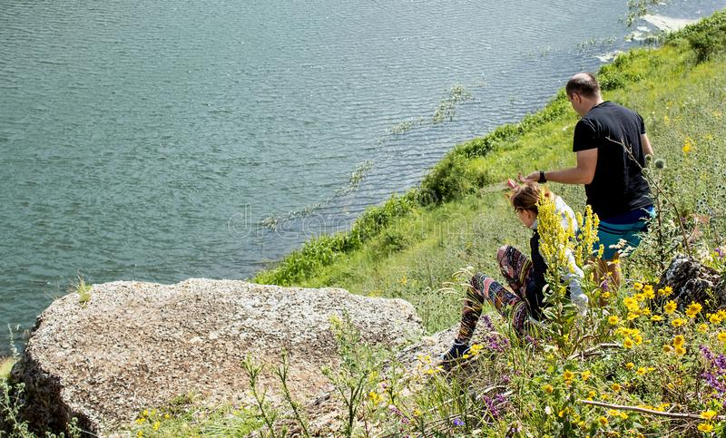 Yelets, Russia, July 2017: A man helps a girl to descend from a slope, look at the river royalty free stock images