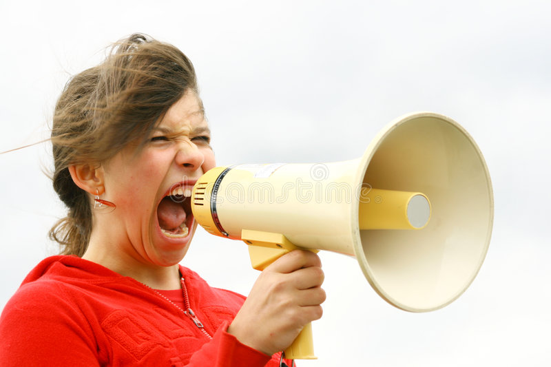 Yelling. Young teen yelling through a speakerphone royalty free stock photo