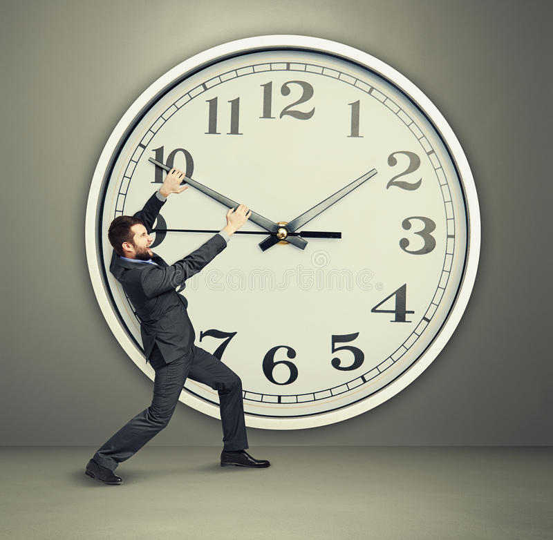 Yelling businessman trying to stop. A time. man and big clock over dark background stock image