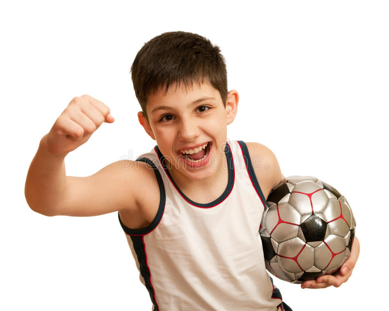 Yelling kid happy of his victory. A happy kid is holding his right fist above his head and a ball in his left hand; isolated on the white background stock photos