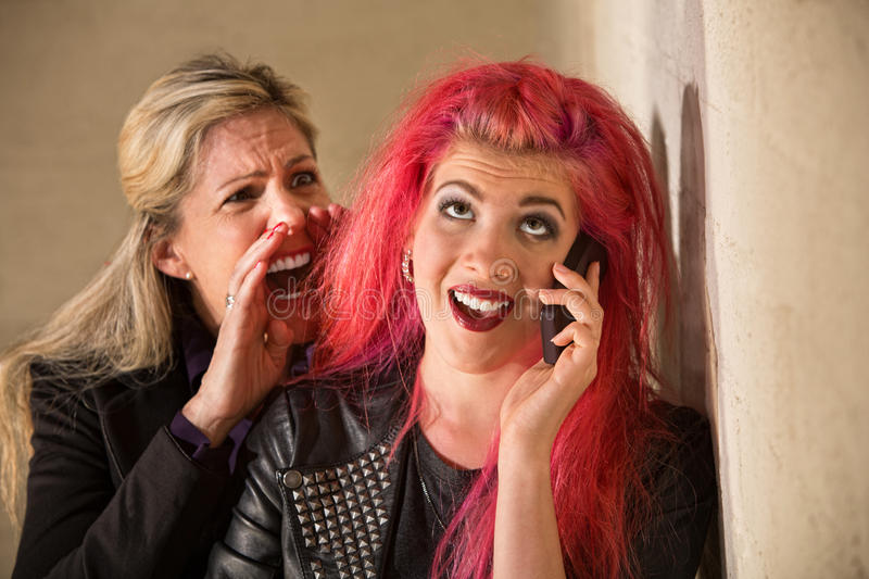 Yelling at Teenage Girl on Phone. Mature women yelling to ear of teenager on phone royalty free stock photography
