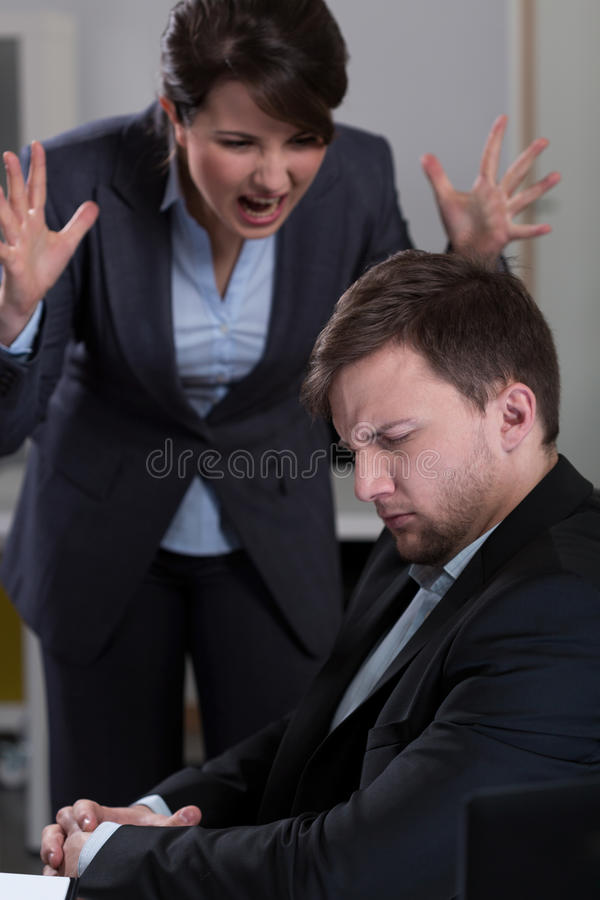 Yelling at worker. Young female boss yelling at her handsome worker stock photo