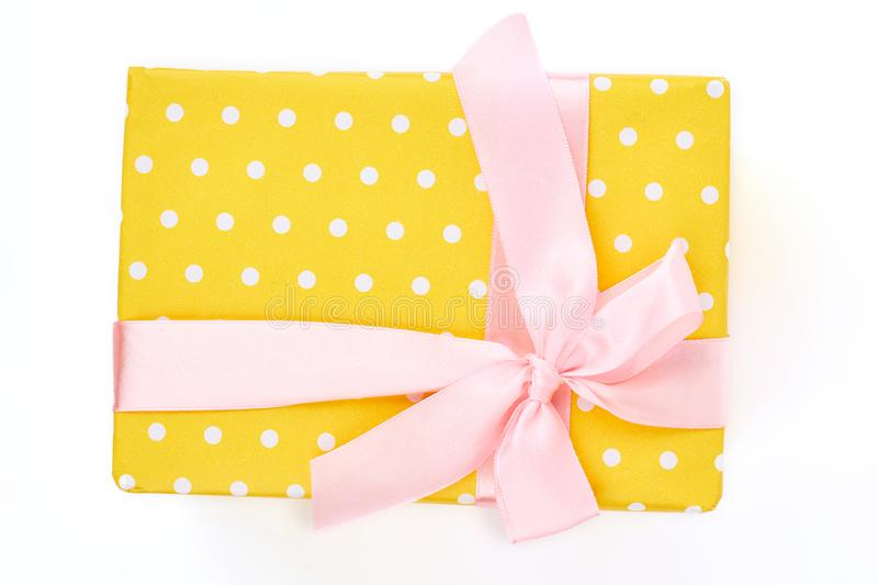 Yello dotted gift box, white background. Box with Christmas present tied with gentle pink satin ribbon isolated on white background, top view stock images