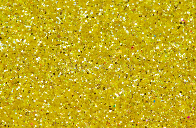 Yellow abstract background. Gold glitter closeup photo. Golden shimmer wrapping paper. Sparkling glitter festive backgrop. Birthday greeting card or wedding stock photography