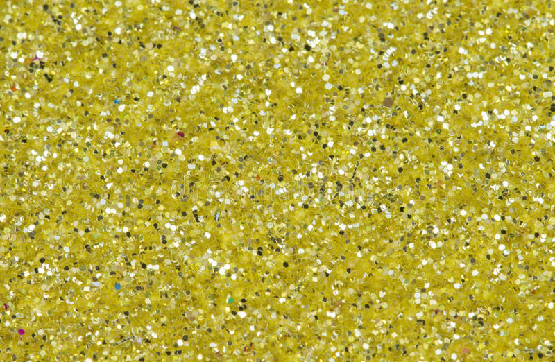 Yellow abstract background. Gold glitter closeup photo. Golden shimmer wrapping paper. Sparkling glitter festive backgrop. Glamour greeting card or wedding royalty free stock image