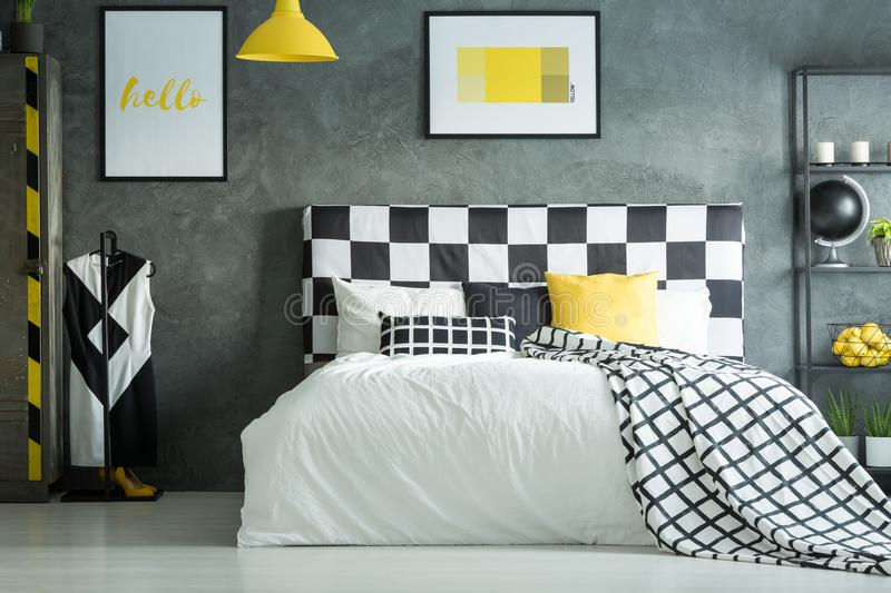Yellow accent in dark bedroom. With shelf, yellow lamp and king-size bed against concrete wall stock images