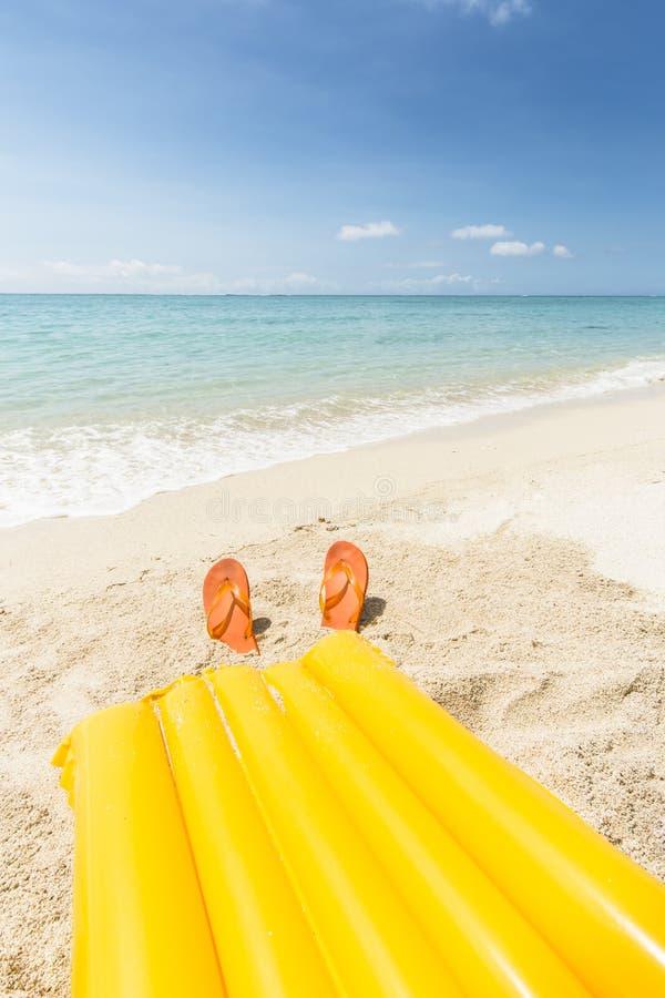 Yellow air mattress and orange flip flops stock photo