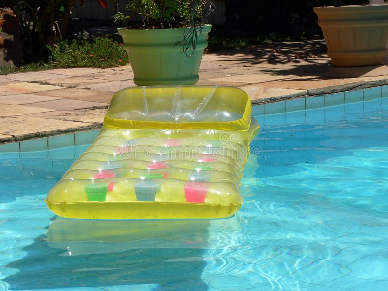 Yellow airbed. A yellow airbed by the side of the swimming pool stock photos