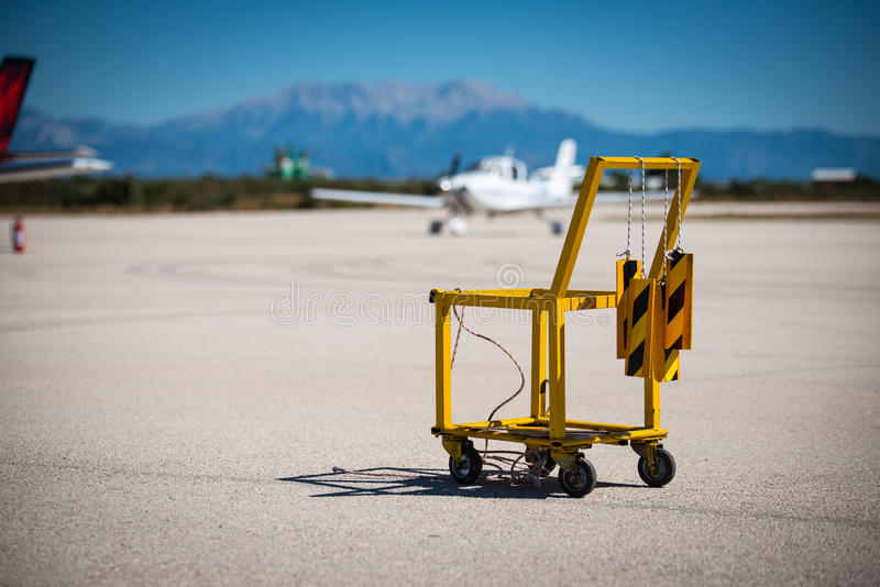 A yellow aircraft chocks and fire extinguisher carrier on a small airport. stock photo