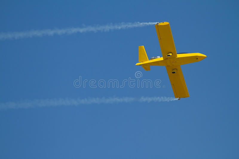 Yellow Airplane Speeds By With Blue Sky Stock Image