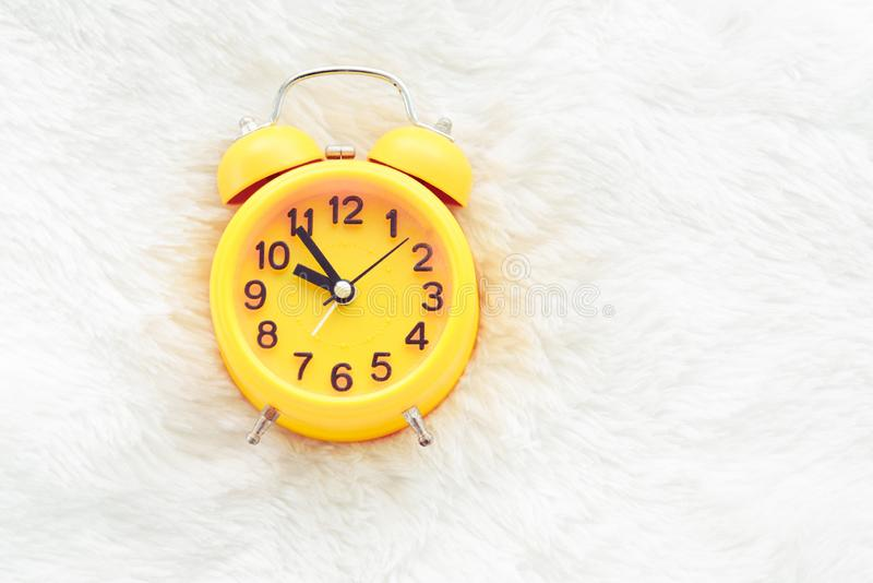 Yellow alarm clock on white wool. Late and Lazy time concept. Morning in holiday theme. Around 10 O Clock stock photography