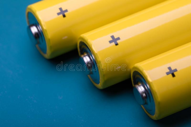 Yellow alkaline batteries on blue background. Close up shot of yellow AA alkaline or rechargeable NiMH batteries on blue background, shallow focus stock photos