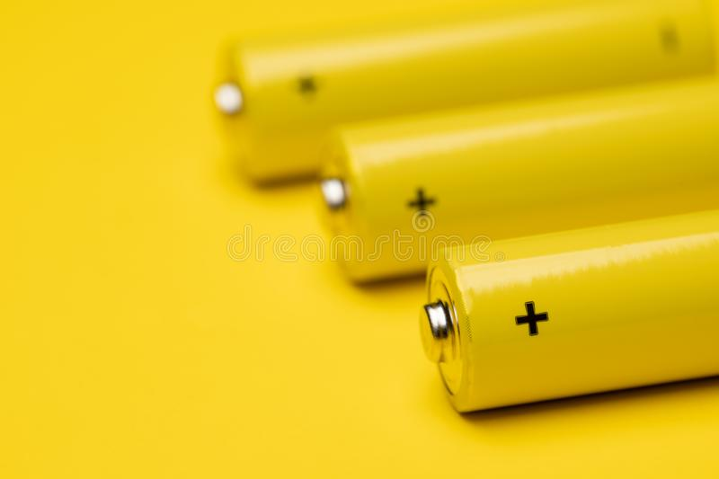 Yellow alkaline batteries colorful background. Close up shot of yellow AAA alkaline or rechargeable NiMH batteries or on yellow background, shallow focus stock photo